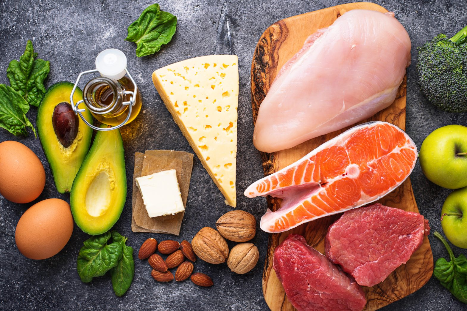 Food board filled with meat, fish, cheese, avocado, eggs, nuts, and dates.