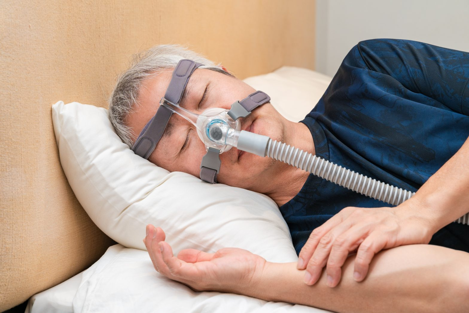 Middle aged man wearing a CPAP nasal mask while in bed.