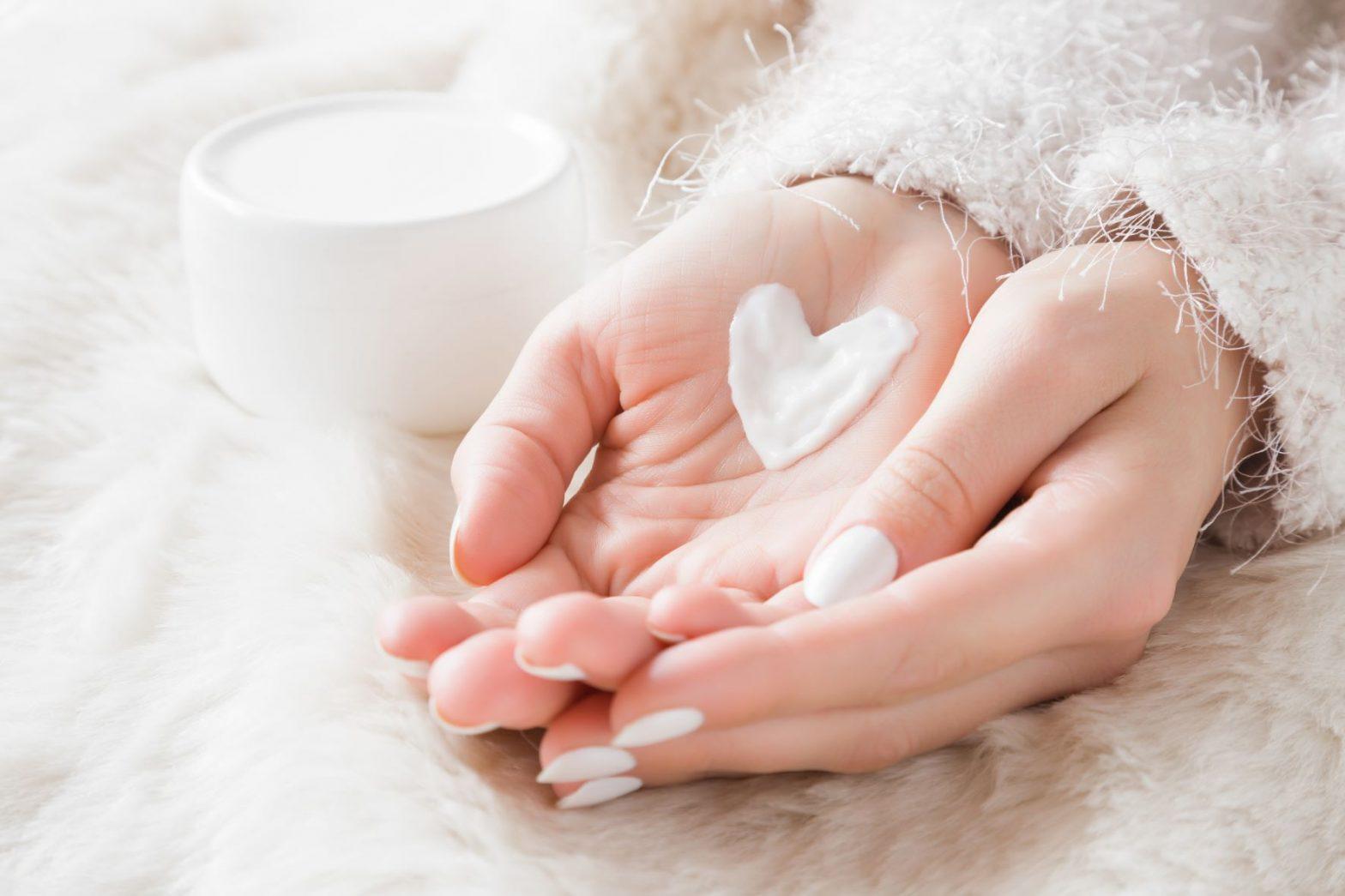 Hands holding skin cream shaped like a heart